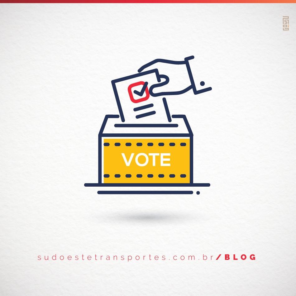 uma mão colocando o voto na urna